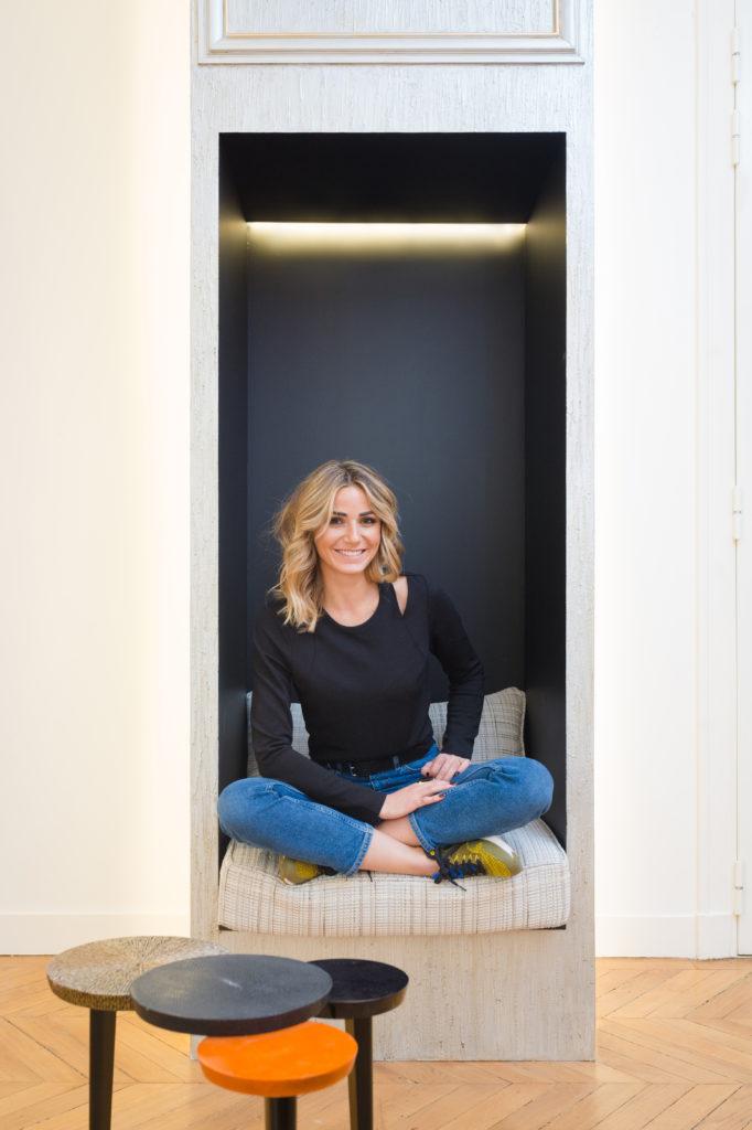 Une femme blonde assise en tailleur avec un jean's et des baskets et un haut noir dans une alcove de maison moderne.