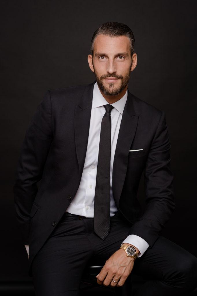 Un homme assis portant un costume sombre éclairé sur fond sombre, une main dans la poche, l'autre sur sa cuisse avec une montre dorée.